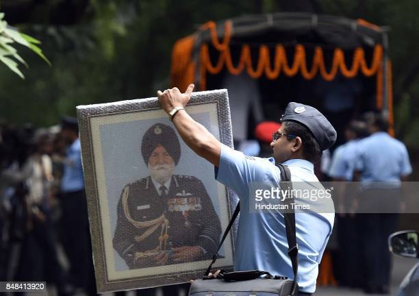 An Air force staff member carrying a portrait in the front of deceased soul of Marshal of the Air Force Arjan Singh the only officer of the Air Force...