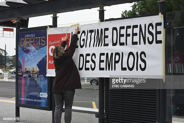 An Air France employee hangs a banner reading 'Jobs selfdefence' during a protest against a restructuring plan that will cut hundreds of jobs next...