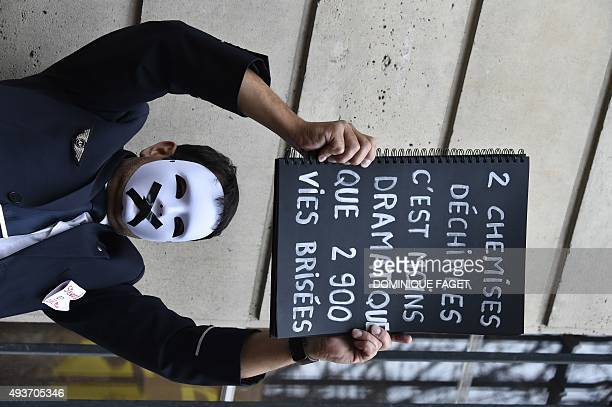 An Air France employee holds up a placard reading 'Two torn shirts are less dramatic than 2900 broken lives' during a demonstration against a...