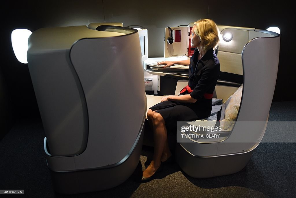 An Air France flight attendant tries out the new business class seating at the new Air France Exhibition called 'Air France,france is in the Air' in New York June 25, 2014. Air France held a news conference unveiling the new Upscale Experience on the Paris-New York route with the new economy, premium economy and business cabins on board Boeing 777's. AFP PHOTO / Timothy A. CLARY