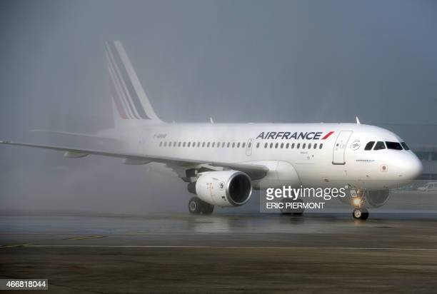 An Air France medium haul Airbus A319 with a new cabin version is greeted by water jets on the tarmac at Roissy Charles de Gaulle airport after its...