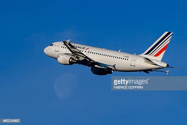 An Air France passenger jetliner takes off from Geneva International Airport as the moon is seen in the distance on December 10 2014 Global airline...