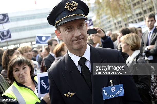 An Air France pilot wears a badge reading 'No to the strike' during a demonstration against the French airline pilots' strike on September 24 2014 in...
