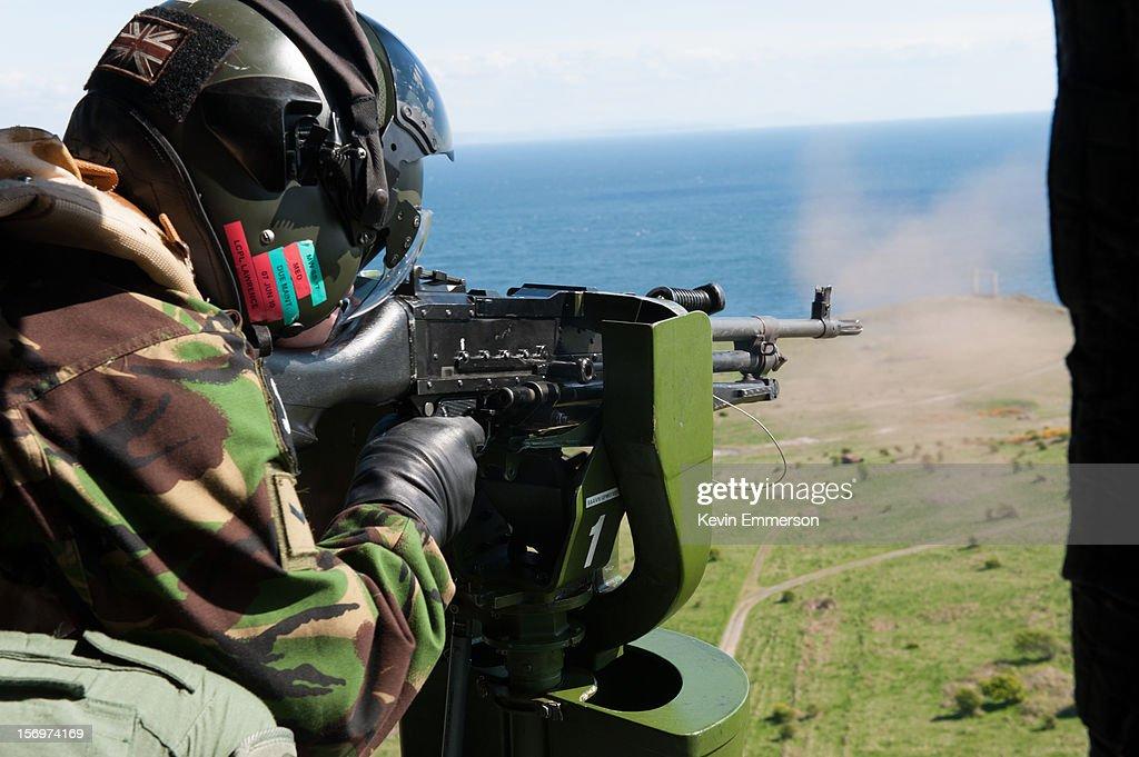 An air gunner fires a General Purpose Machine Gun (GPMG) from an Army Air Corps, Lynx AH7 helicopter.