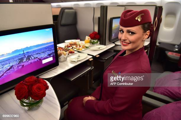 An air hostess sits in the 'QSuite' business class of a Qatar Airways Boeing 777 jet airliner on display at the International Paris Air Show in Le...