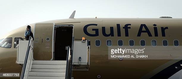 An air hostess stands by a Gulf Air plane on display during the opening of the Bahrain International Airshow 2014 in Sakhir south of the capital...