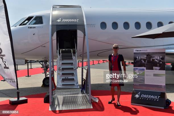 An air hostess stands outside a Dassault Aviation Falcon 900 LX jet on display at the International Paris Air Show in Le Bourget outside Paris on...