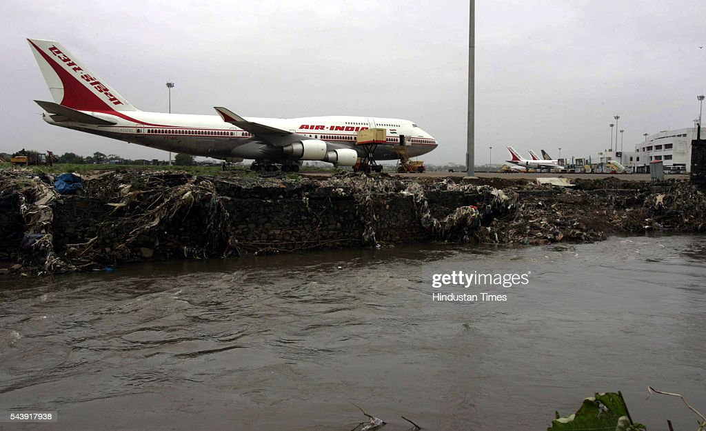 An Air India aircraft sits on the edge of the airport. With several sections of the airport's boundary wall broken because the Mithi River overflowed.