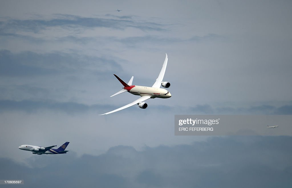 An Air India Boeing Dreamliner (C) crosses a Thai Airway Airbus A 380 (bottom in the background) flying over Le Bourget airport with two other jets, near Paris on June 20, 2013 during the 50th International Paris Air show.