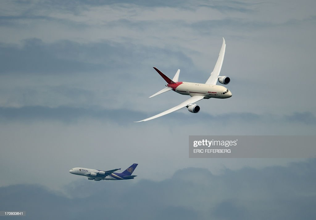 An Air India Boeing Dreamliner (R) flies by a Thai Airway Airbus A 380 (bottom in the background)over Le Bourget airport , near Paris on June 20, 2013 during the 50th International Paris Air show.