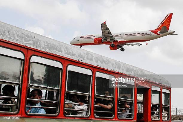 An Air India Ltd aircraft flies over a bus as it prepares to land at Chhatrapati Shivaji International Airport in Mumbai India on Thursday May 23...