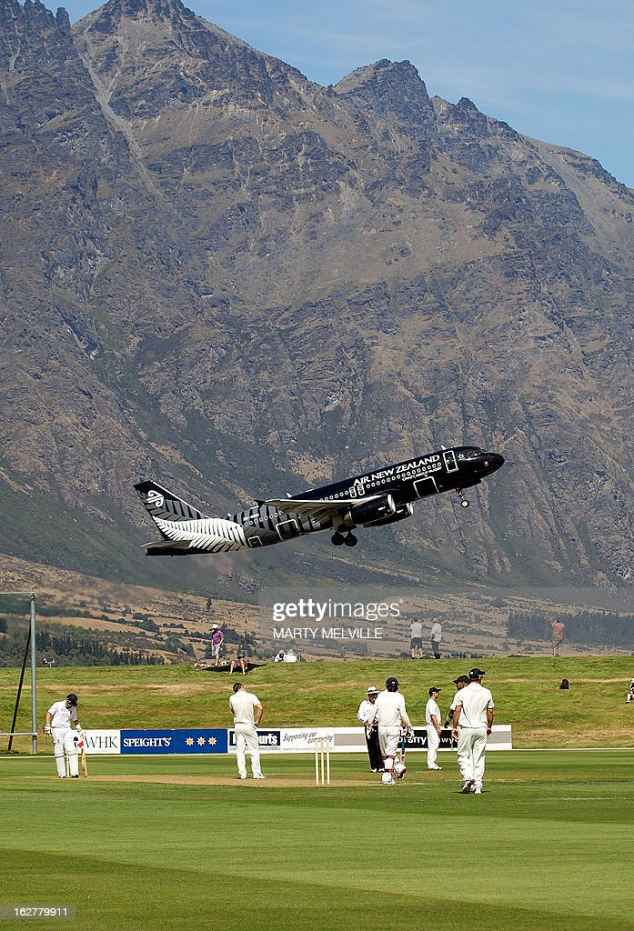 An Air New Zealand jet takes off above the cricketers during day one of the four day warm up International cricket match between New Zealand and England played at the Queenstown Event Center in Queenstown on February 27, 2013. AFP PHOTO / Marty MELVILLE