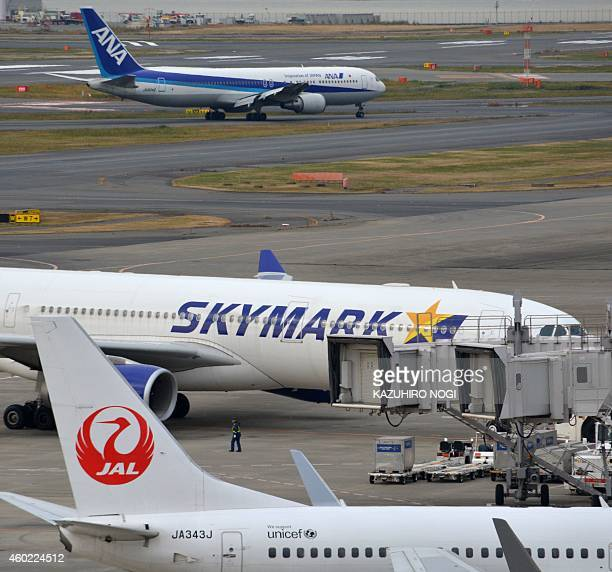 An Air Nippon Airways plane taxis past Skymark Airlines and Japan Airlines passenger jets at Tokyo's Haneda airport on December 10 2014 Struggling...