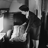 An air stewardess displays a parachute inside the Vickers Viking airplane previously used by Queen Elizabeth II 12th August 1958