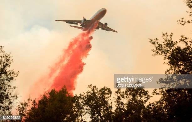 An air tanker drops fire retardant on flames as firefighters continue to battle against the Detwiler fire in Mariposa California on July 19 2017 The...