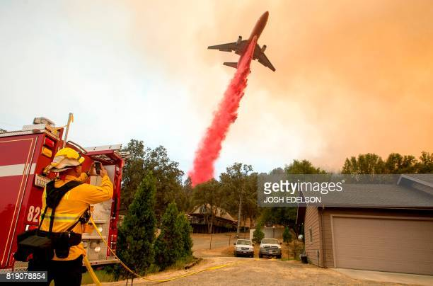 TOPSHOT An air tanker drops fire retardant on flames as firefighters continue to battle against the Detwiler fire in Mariposa California on July 19...