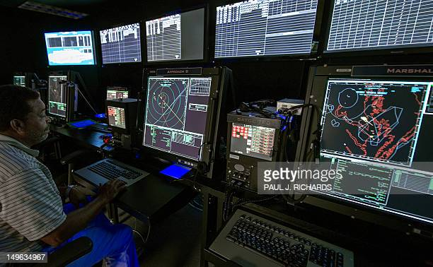 An Air Traffic Controller monitors computer screens inside the Carrier Air Traffic Control Center used with the US Navy's Northrop Grumman X47B a...