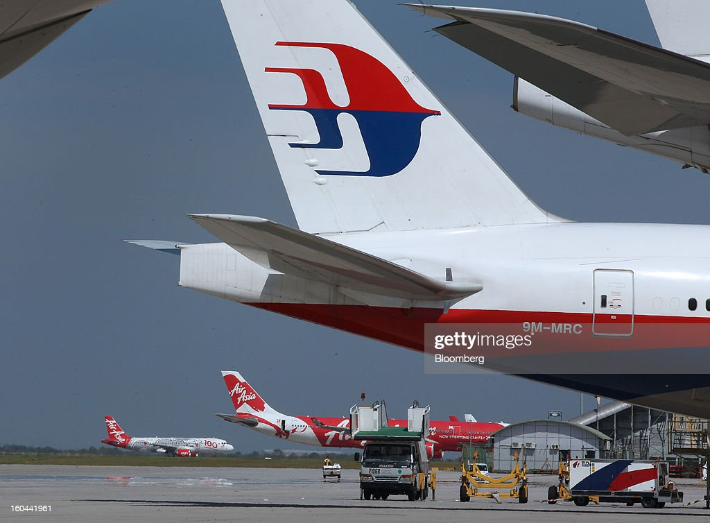 An AirAsia Bhd. aircraft, left, lands while another AirAsia aircraft stands on the tarmac behind a Malaysian Airline System Bhd. (MAS) aircraft at Kuala Lumpur International Airport (KLIA) in Sepang, Malaysia, on Thursday, Jan. 31, 2013. Malaysia Airlines joins the Oneworld airline alliance tomorrow. Photographer: Goh Seng Chong/Bloomberg via Getty Images