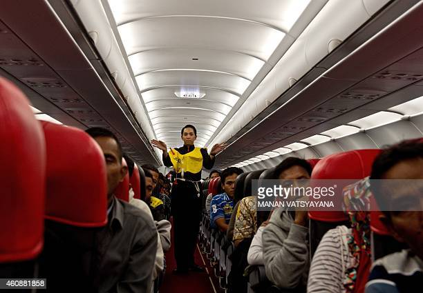 An AirAsia flight attendant gives a safety demonstration while onboard a flight preparing to depart from Kuala Lumpur to Surabaya at Kuala Lumpur...