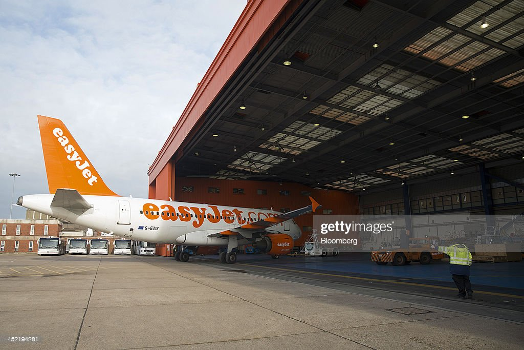 An Airbus A319 aircraft, operated by EasyJet Plc, is pushed by a tractor from a maintenance hangar at the airline's hub at London Luton Airport in Luton, U.K., on Tuesday, Nov. 26, 2013. Shares in International Consolidated Airlines Group SA (IAG) and EasyJet Plc climbed at least 2 percent, pushing a gauge of travel and leisure companies higher, as oil prices slid in reaction to Iran's nuclear deal with world powers. Photographer: Simon Dawson/Bloomberg via Getty Images