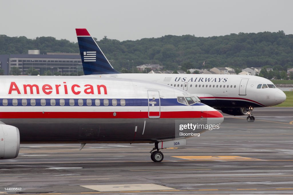 An Airbus A319, operated by US Airways Group Inc., back right, taxis after landing behind a Boeing Co. 737, operated by AMR Corp.'s American Airlines, at Reagan National Airport in Washington, D.C., U.S., on Tuesday, May 8, 2012. American Airlines gave more details of its strategy as US Airways Group Inc. steps up pressure for a possible takeover bid. Photographer: Andrew Harrer/Bloomberg via Getty Images