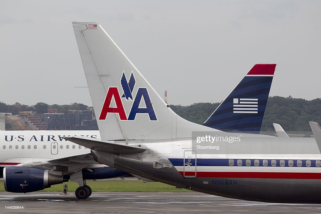 An Airbus A319, operated by US Airways Group Inc., back, taxis after landing behind a Boeing Co. 737, operated by AMR Corp.'s American Airlines, at Reagan National Airport in Washington, D.C., U.S., on Tuesday, May 8, 2012. American Airlines gave more details of its strategy as US Airways Group Inc. steps up pressure for a possible takeover bid. Photographer: Andrew Harrer/Bloomberg via Getty Images