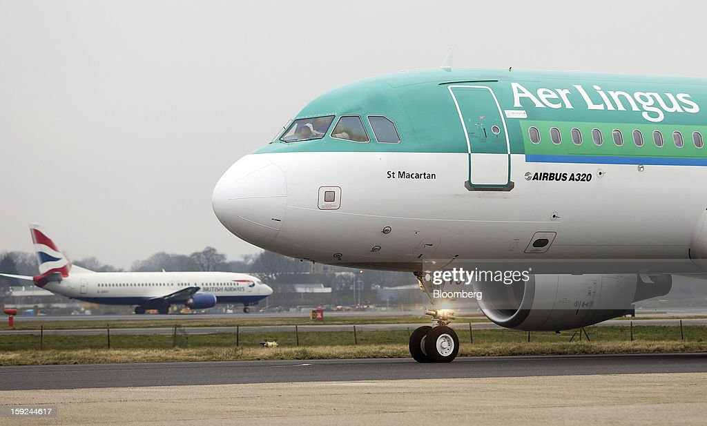 An Airbus A320 aircraft, operated by Aer Lingus Group Plc, right, passes a British Airways aircraft at Gatwick airport in Crawley, U.K., on Thursday, Jan. 10, 2013. Gatwick, acquired by Global Infrastructure Partners Ltd. in 2009 after regulators sought a breakup of BAA Ltd., owner of the larger Heathrow hub, is 30 miles (48 kilometers) south of London and serves about 200 destinations, more than any other U.K. airport, according to flight schedule data provider OAG. Photographer: Chris Ratcliffe/Bloomberg via Getty Images