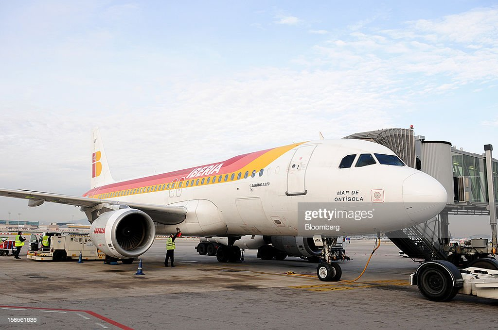 An Airbus A320 operated by Iberia, a unit of International Consolidated Airlines Group SA (IAG), is prepared for flight at EL Prat airport in Barcelona, Spain, on Wednesday, Dec. 19, 2012. International Consolidated Airlines Group SA won't require European Union approval to buy 100 percent of low-cost carrier Vueling Airlines SA, the EU's antitrust chief said. Photographer: Stefano Buonamici/Bloomberg via Getty Images