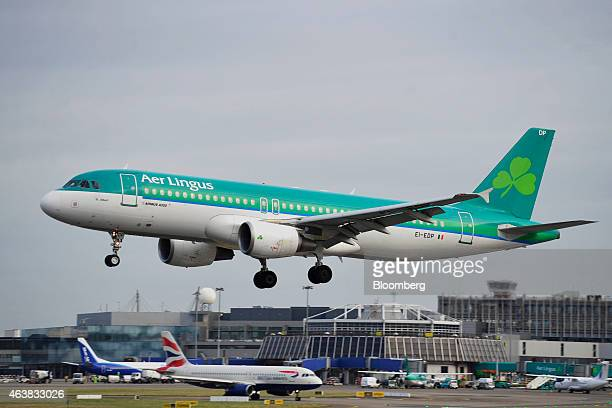 An Airbus A320 passenger aircraft operated by Aer Lingus Group Plc passes above a passenger aircraft operated by British Airways a unit of IAG SA as...