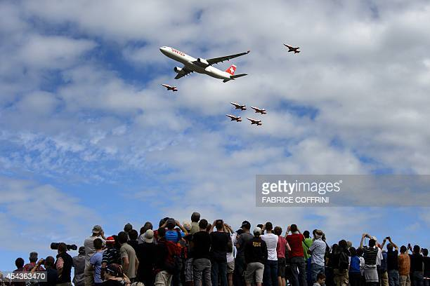 An Airbus A330 commercial plane of Swiss International Air Lines flies with fighter jets of the 'Patrouille Suisse' on August 30 2014 during the...