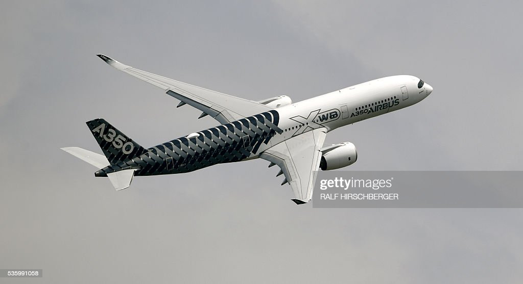 An Airbus A350 flies over the International Aerospace Exhibition (ILA) in Schoenefeld on May 31, 2016. The Aerospace Exhibition at Schoenefeld Airport near Berlin takes place from June 1 till 4. / AFP / dpa / Ralf Hirschberger / Germany OUT