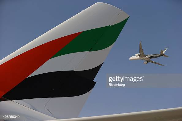 An Airbus A350 XWB flies past the tail fin of an Airbus A380800 operated by Emirates Airline during an aerial display on the opening day of the 14th...