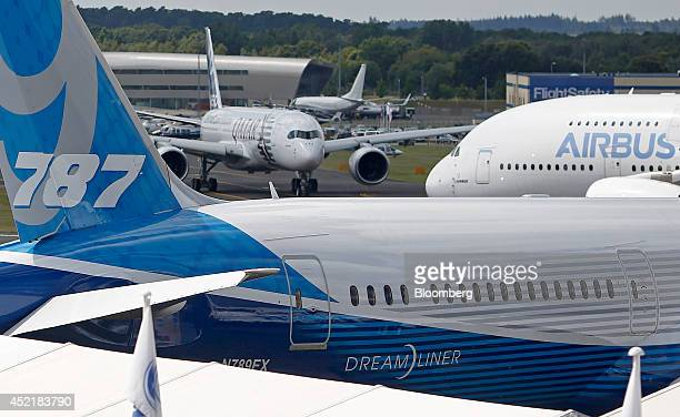An Airbus A380 aircraft produced by Airbus Group NV right taxis past a Boeing 7879 Dreamliner aircraft produced by Boeing Co before performing in an...