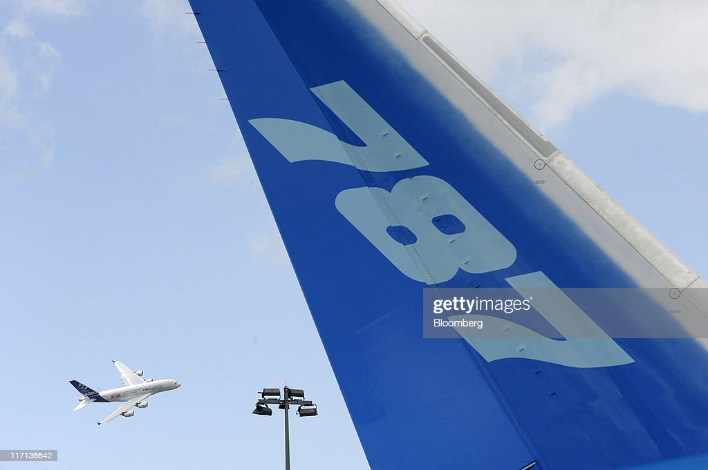 An Airbus A380 airliner, left, passes a Boeing 787 Dreamliner tailfin during a demonstration flight at the Paris Air Show in Paris, France, on Thursday, June 23, 2011. The 49th International Paris Air Show, the world's largest aviation and space industry show, takes place at Le Bourget airport June 20-26. Photographer: Fabrice Dimier/Bloomberg via Getty Images