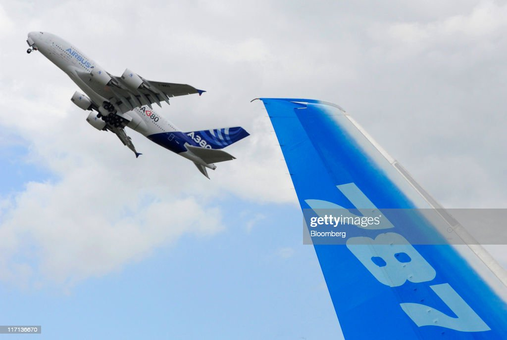 An Airbus A380 airliner, left, passes a Boeing 787 Dreamliner tailfin, before making a demonstration flight at the Paris Air Show in Paris, France, on Thursday, June 23, 2011. The 49th International Paris Air Show, the world's largest aviation and space industry show, takes place at Le Bourget airport June 20-26. Photographer: Fabrice Dimier/Bloomberg via Getty Images