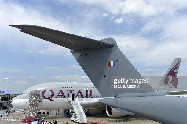 An Airbus A380 of Qatar Airways and the tailplane of an Airbus A400M military airplane are pictured at Le Bourget airport on June 16 north of Paris...