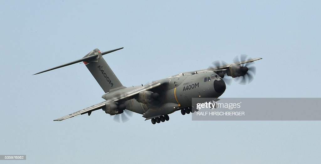 An Airbus A400M flies over the International Aerospace Exhibition (ILA) in Schoenefeld on May 31, 2016. The Aerospace Exhibition at Schoenefeld Airport near Berlin takes place from June 1 till 4. / AFP / dpa / Ralf Hirschberger / Germany OUT