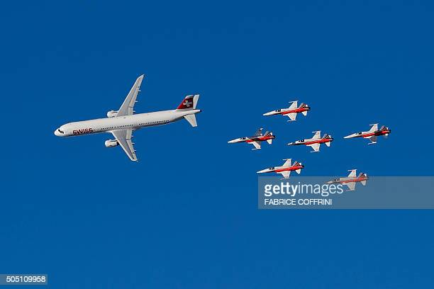 TOPSHOT An Airbus commercial plane of Swiss International Air Lines flies with fighter jets of the 'Patrouille Suisse' during the Alpine skiing FIS...