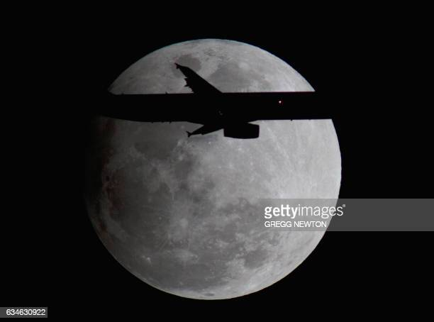An Airbus passenger jet on final approach to Orlando International Airport transits past a full 'snow' moon during the penumbral eclipse on February...