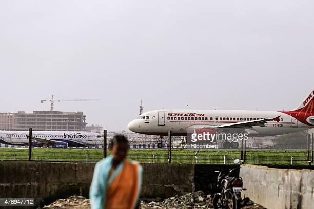 An Airbus SAS A319 aircraft operated by Air India Ltd taxies in front of an aircraft operated by IndiGo at Chhatrapati Shivaji International Airport...