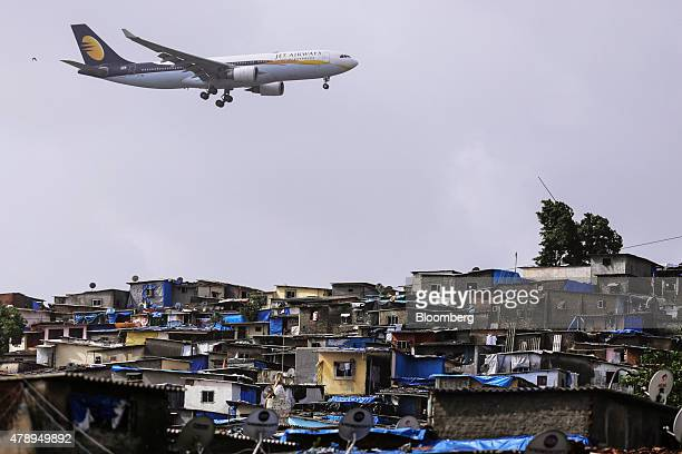 An Airbus SAS A330202 aircraft operated by Jet Airways India Ltd flies over slum housing as it approaches to land at Chhatrapati Shivaji...