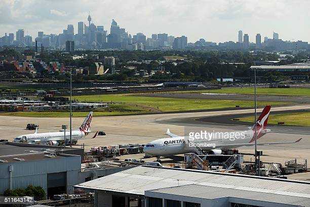 An Airbus SAS A330300 aircraft operated by Qantas Airways Ltd right and a Boeing Co 737800 aircraft operated by Virgin Australia Holdings Ltd stand...