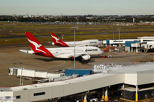 An Airbus SAS A380 front and a Boeing 747 aircraft both operated by Qantas Airways Ltd stand at the International terminal at Sydney Airport in...
