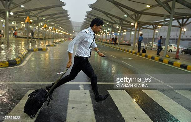 An aircraft crew member runs with his baggage in a heavy monsoon rainstorm at Indira Gandhi International Airport in New Delhi on July 7 2015 PHOTO /...