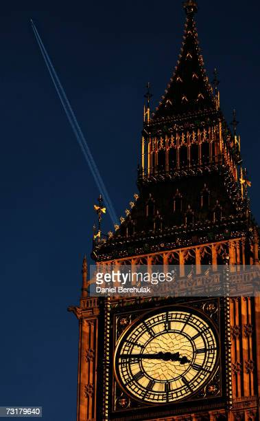 An aircraft flies behind St Stephens Tower also known as Big Ben leaving vapour trail on January 31 2007 in London England When burning its fuel...