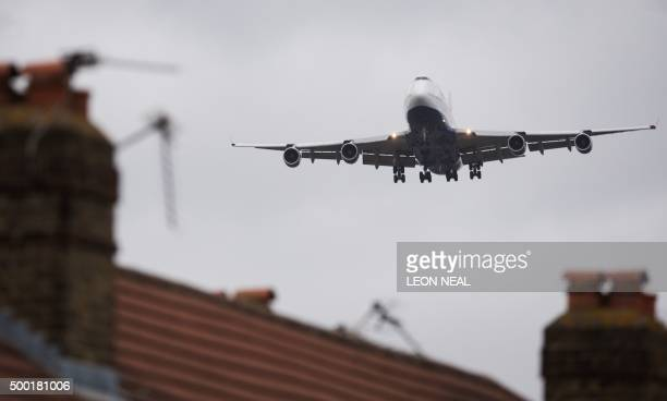 An aircraft flies over residential houses in Hounslow as it prepares to land at London Heathrow airport on December 5 2015 British Prime Minister...