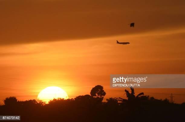 An aircraft flies over the setting sun in Siliguri on November 14 2017 / AFP PHOTO / DIPTENDU DUTTA