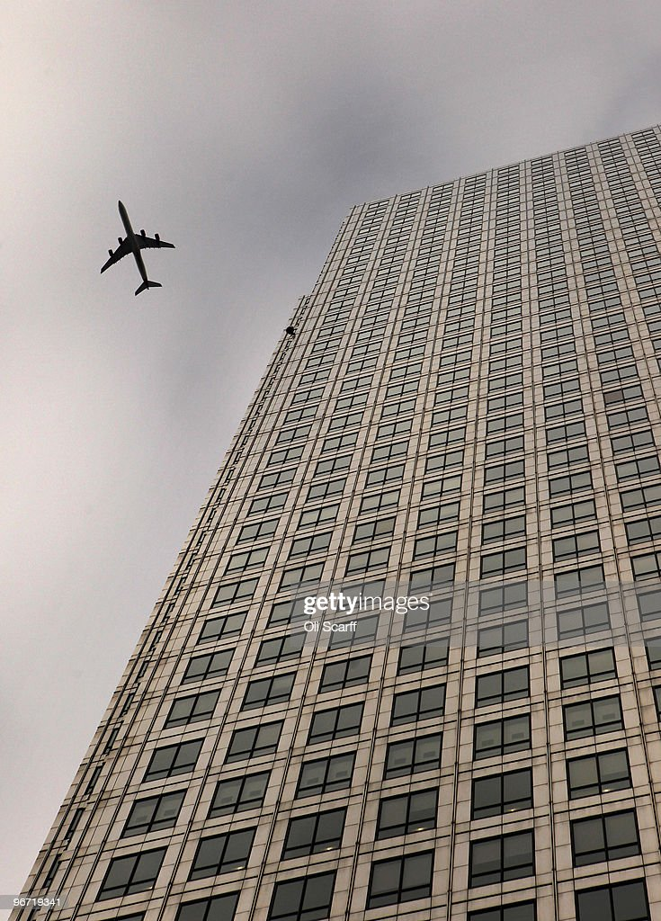 An aircraft flies over the skyscraper 'One Canada Square' in Canary Wharf on February 15 2010 in London England As the UK gears up for one of the...