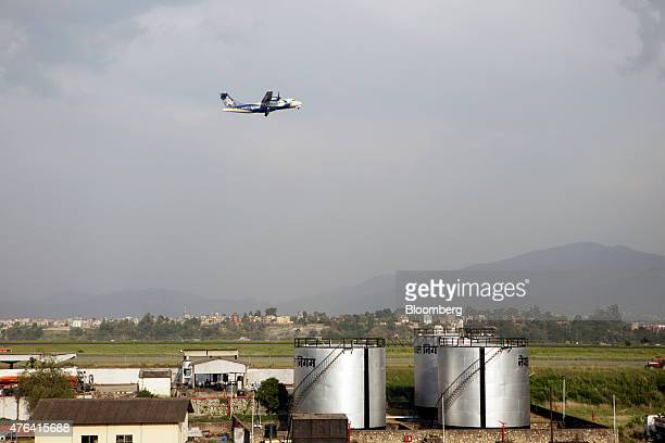 An aircraft flies overhead as Nepal Oil Corp storage tanks sit at the airport in Kathmandu Nepal on Wednesday June 3 2015 Nepal's gross domestic...