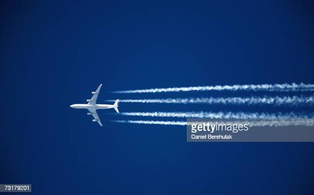 An aircraft flies through London skies leaving a vapour trail on February 2 2007 in London England When burning its fuel planes release exhaust fumes...